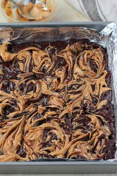 The BEST Peanut Butter Brownies! Fudgy brownies filled with peanut butter cups and topped with a peanut butter swirl. #peanutbutter #brownies #dessert #chocolate #peanutbuttercups