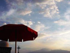 Castelmola (ME) - Sguardo in controluce sull'Etna, dalla terrazza sul tetto del Bar Turrisi. In primo piano elementi architettonici della Chiesa Madre - Etna from the roof terrace of the Bar Turrisi. In the foreground some architectural elements of the Mother Church.