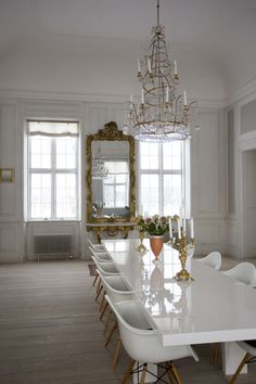 White lacquered table + Eames chairs + crystal spiral twist chandelier.