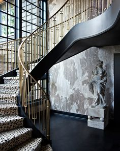 Dramatic staircase with custom brass railing for a home on Mercer Island, Washington. The wallpaper is by Porter Teleo.