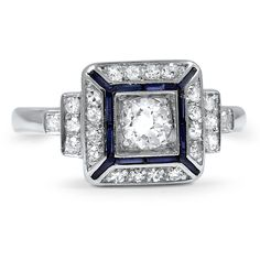 The Shanon Ring ~ Art Deco ring features an old European cut Diamond and twenty-four single cut Diamond accents in a tiered Platinum setting. Twelve baguette cut lab created Sapphires perfectly accent the center gem for a regal finish. c1920's