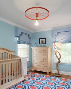 The parents are avid bicycle riders, and they wanted their son's room to reflect their love. The bicycle ceiling fixture is painted a bold orange to match the colorful area rug, and a rope floor lamp is topped with a playful bicycle lamp shade. Light wood furniture is the perfect complement to the bold colors of the space.