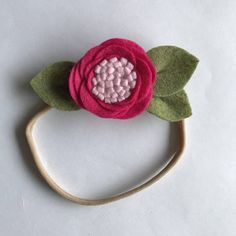 This handmade hot pink felt flower with light pink center headband with leaves measures 4 inches long x 2 inches wide and comes on a soft nude nylon headband or alligator clip. Please select your choice from the drop down menu. Your single flower headband or alligator clip will ship in
