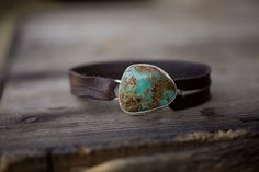 "A beautiful Nevada Turquoise nugget in shades of green, blue and brown is wrapped sterling silver.  The nugget seconds as a closure for a .50"" strap of distressed chocolate brown leather.Nugget 1x1""*This is a one of kind, please select desired size at checkout."
