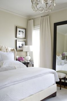 Amazing makeover: love the bed, nightstand, lamp, mirror, black + white photos, white + cream color scheme + drapes . For the guest room?
