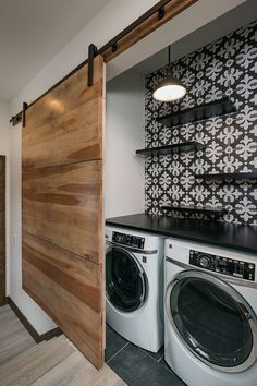 Laundry Room Closet Hallways - Hallway laundry closet with custom modern tile, floating shelves, pendant light, behind an oversized custom barn door #laundryroomclosethallways