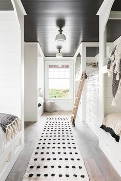 Two vintage schoolhouse flush mounts mounted to a black shiplap ceiling over a black and white runner in a black and white bunk room.