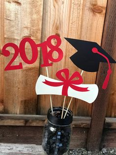 What a fabulous way to accent your Graduates big day! This charming Graduation Centerpiece is the perfect addition to your Graduation Partys table decor. Graduation Centerpiece includes: -Graduation Cap -Diploma -2018 All are placed on different length wood picks, so that they