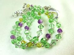 This green, purple, and citrine three stranded bracelet is composed of Peridot and Chrysolite Swarovski crystals, amethyst gemstones and citrine colored crystals. Mostly made of Swarovski Peridot and