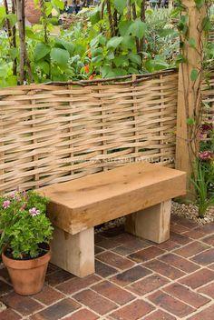 Wooden garden bench against willow woven fence in garden by judywhite