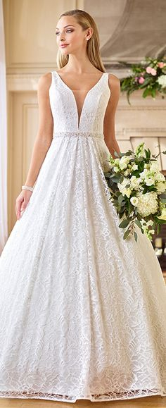 The epitome of modern day royalty, this sleeveless allover lace and organza ball gown features a curved deep V-neckline with an illusion inset, a beaded belt at the natural waist, a dramatic large keyhole back finished with covered buttons that cascade down to the hemline, and a voluminous box pleated skirt with pockets and a …