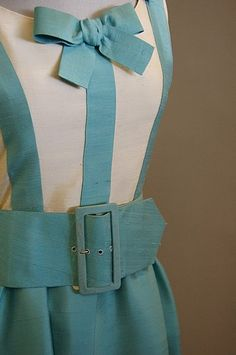 A Jean Patou Paris turquoise and ivory slubbed silk dress, late 1960s, labelled and numbered 86453, the bodice trimmed with bows to front and back and shoulders, deep flounced hem, broad belt. Detail