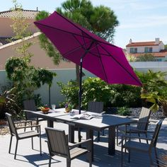 Un parasol inclinable au centre de la table de jardin
