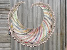 Passe-partout's Color Crescent - pattern by Kieran Foley -- A swirling crescent of rainbow stripes inspired by little patches of bright color on insect wings.  It's a challenging knit with lace stitches on RS and WS rows, stranding, intarsia, and long multicolored rows - a good project for using up leftovers of interesting colors or variegated yarns.