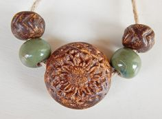 Set bead-lentil brown flower. Beads made of stoneware , this set consists of : 1bead-lentil , with a hole in the center,these bead are hollow and weigh very little ,the bead has brown glaze , measures 28 x 28 mm. 2 hand-carved beads ,have brown glaze , measures 12 x 12 mm. 2 round beads , have green glaze , measures 12 x 12 mm. By Mª Carmen Rodriguez Martinez ( Majoyoal ) https://www.facebook.com/groups/CeramicArtBeadMarket/