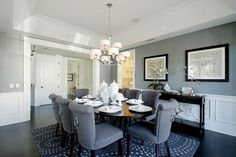 Bluish-gray dining room with picture molding and dark wood floors