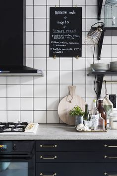 Black cabinets, gold hardware, & white tile in the kitchen