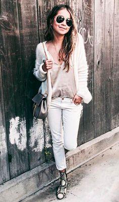 Street style look com blusa bege e calça branca.