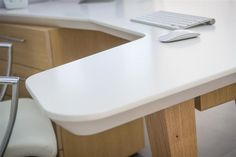 Λεπτομέρεια γραφείου με λευκή λακαριστή επιφάνεια εργασίας και δρύινο σκελετό με…