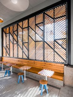 A cedar screen with the Houndstooth identity graphic faces the street to enhance the brand's public presence. Break stools with blue bases and cafe tables by OFFICIAL offer additional seating options.  (Courtesy Robert Yu and Mark Leveno)