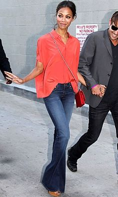 Zoe Saldana in a vibrant orange silk shirt with skinny denim flares and a cross-body bag