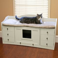Cat beds furniture. Top has cushioned area for kitty to lounge. Hide her litter box in the center that has a flip door. Keep cat toys, litter scoops and meal accessories in the additional storage on the sides. A unique cat bed!