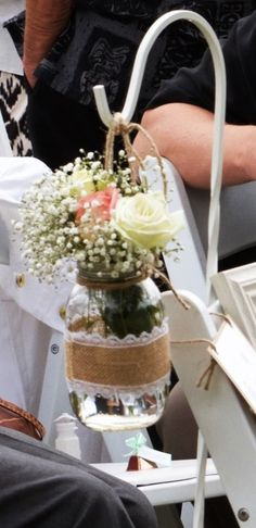 Hand crafted mason jar vases with burlap and lace hanging on a white sheppard's hooks that lined the aisle. Flowers provided by Alluvion in Haleiwa, HI.