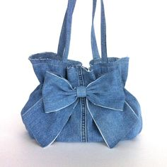 This Eco friendly bow purse is constructed from recycled dark blue denim (jean pant) and is girly and practical. I left some edges unfinished, and embellished it with a big bow on front side.This bag has a reinforced oval shape base, elasticized opening, and it is fully lined with a