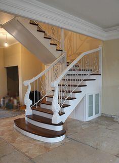 Деревянная двухмаршевая лестница с забежными ступенями и кованым ограждением