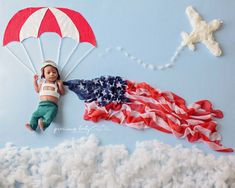 Adorable African American newborn baby boy parachuter holding a flag (scarf). Dad is in US Air Force, military. United States flag (scarf). Baby ImaginArt by Angela Forker. Precious Baby Photography. Creative, unique, whimsical, amazing, funny photography. New Haven, Fort Wayne, Indiana.