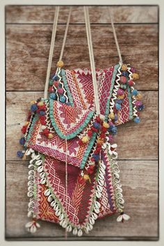Pretty vintage Indian embroidered bags. Love the pom-poms and cowry shells.  I bet I could make this. I could even use some old coins.