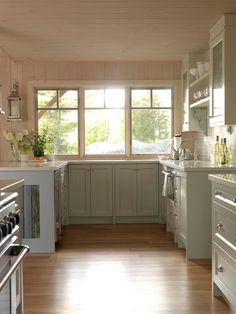Lovely light blue cabinets fill this cottage kitchen. Large windows provide abundant natural light in a warm, weathered space that is signature of Cottage design.