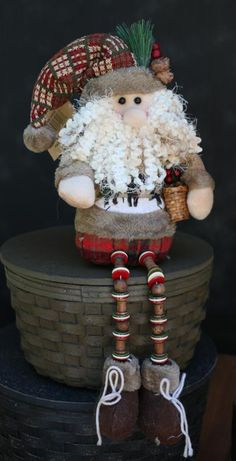 Alpine Santa with Button Legs, by Hanna's Handiworks. Has a weighted base for sitting securely on a shelf, and button/bead legs that dangle. Measures approx 13 inches. Made of knit fabric, pinecones, twigs, buttons, felt, etc. Other stuffed figures also available!