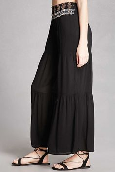 A pair of semi-sheer woven palazzo pants featuring a smocked waistband with geo patterned topstitching and a tiered design. This is an independent brand and not a Forever 21 branded item.