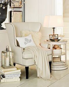 great styling around wingback- lantern on stack of books, side table with greek key lamp, throw