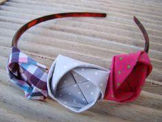 arquinho de cabelo com 3 fuxicos de origami em tecidos coloridos. obs: o arquinho pode ser de plástico, acrílico, metal ou revestido com tecido. tamanho único. Talvez não sirva para crianças menores de 5 anos. medida de cada fuxico: 4 cm x 4 cm. R$ 18,80