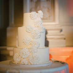 The ivory cake was topped with pearl piping and sculpted fondant designs to match the bride's dress.