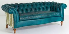 This gorgeous turquoise chesterfield sofa will make more than a statement in your home.  Features rolled arms, brown turned legs, and a striking print on its back. Upholstered in high quality top grain leather and constructed by way of eight-way hand-tied spring suspension , the quality and comfort with matches this sofa's good looks!  Expertly made in the United States to last many years. This couch is perfect for your living room.