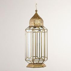 """Get to know the many sides of our Metal Facet Glass Lantern. Handcrafted in India with a traditional Moroccan shape and carved metal accents, this beautifully oversized lantern is perfect for casual or formal décor. It holds one 3"""" diameter pillar candle, and really comes to life when lit."""