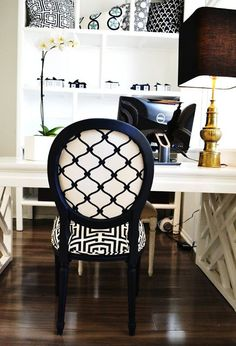 COCOCOZY HQ office space with a vintage brass Stiffel lamp and white orchid sitting on a White Laquer Fertwork Parsons Desk, navy Louis chair with COCOCOZY Logo linen on the front and COCOCOZY Fence in navy on the back