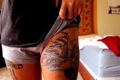Colorful ship thigh tattoo