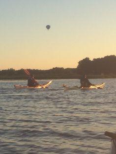 Kayak paddlers and air balloon in symbiosis at lake Hjälmaren, Sweden.