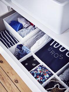 Tiroir ouvert avec vêtements rangés dans des compartiments.