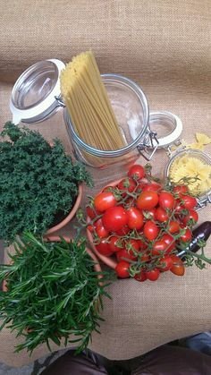 Table rustic set up decor with red tomatoes, pasta abd aromatic herbs