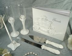"""Give the finishing touches to your wedding with this enchanted Fairy Tale themed bridal accessory set. Each piece is hand crafted in elegant white poly resin with rhinestone accents. The 4 piece set includes an 8"""" x 10"""" guest book, two 9.5"""" x 2.5""""D toasting flutes, a 2.75""""L x 2.75""""W x 1.75""""H pen set and a 10.5"""" cake and 13"""" knife set and all pieces are packaged in design printed clear top boxes."""