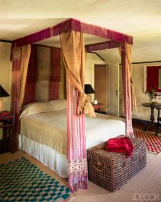The canopy in a guest room is made from 19th-century Bhutanese monks' robes and sashes, the 19th-century trunk is from Singapore, the hooked rugs are from Kenya, and the plaster walls are original to the house.