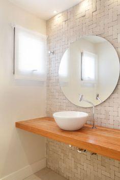 O estilo rústico na decoração, do qual o morador é fã, guiou a arquiteta Letícia Araujo na elaboração deste banheiro. Por isso, para combinar com a escolha do morador de revestir a parede com pedra porosa, a profissional optou por colocar uma bancada de pinho.