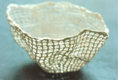 Suzanne Feldt has created products by knitting forms in pure wool that are coated with porcelain and fired at 1650 degrees Fahrenheit - the wool is burned away and the ceramic mesh is kept intact.