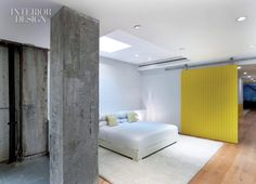 white space with concrete columns and a fab bright yellow barn door! love!