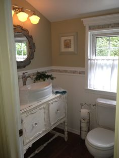 Turn a 1970s mess into a sweet cottage bathroom with an old, refinished cabinet turned into a vanity.